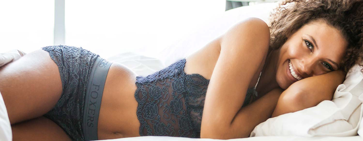 Jordan lounging in bed wearing the FOXERS charcoal gray lace boxers and matching cropped lace camisole